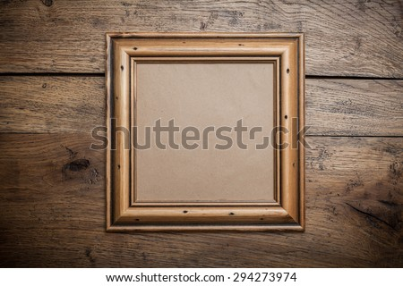 Sqare wooden frame with kraft paper on the old wood background