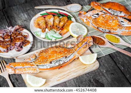 Sqide,jumbo crab and shrimp on dark background - stock photo