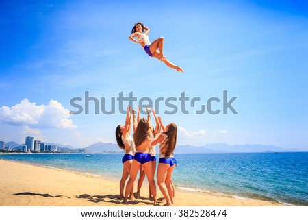 squad of cheerleaders in white blue uniform performs stunt Basket Toss on beach against azure sea and resort - stock photo