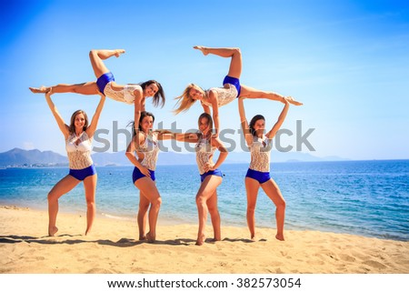 squad of six cute cheerleaders in white blue uniform performs Swedish falls on beach against azure sea - stock photo