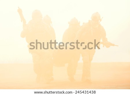 Squad of soldier evacuate the injured fellow in arms hiding in the smoke - stock photo