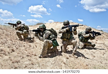 Squad of soldiers in the desert during the military operation - stock photo