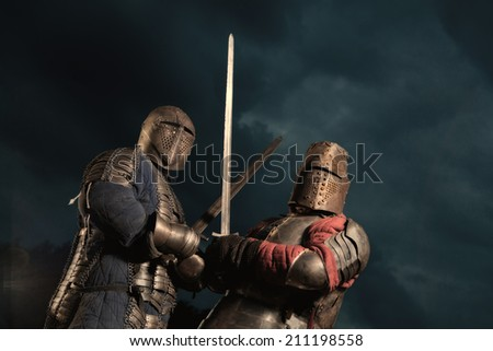 Squad of two medieval knights on the night rural background - stock photo