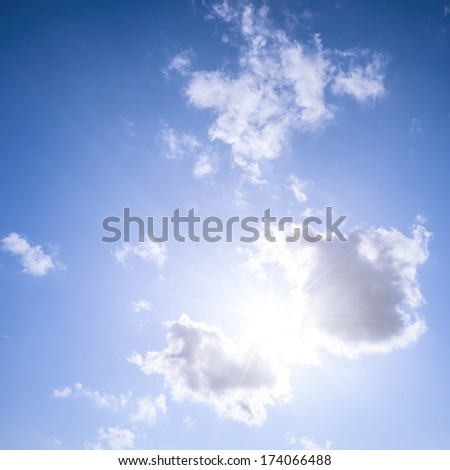 Square blue sky background with bright sun flare shining through clouds