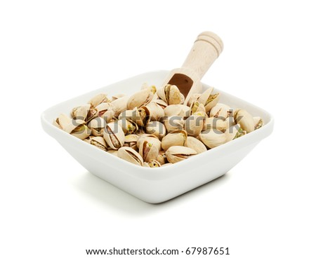 square bowl filled with pistachios and wooden shovel isolated on white - stock photo