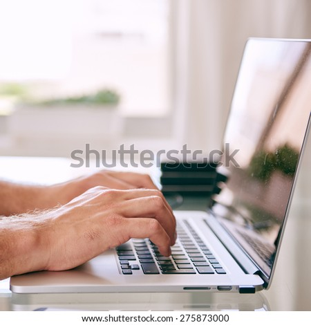 square close up image of hands busy working on a modern laptop computer with copy space - stock photo