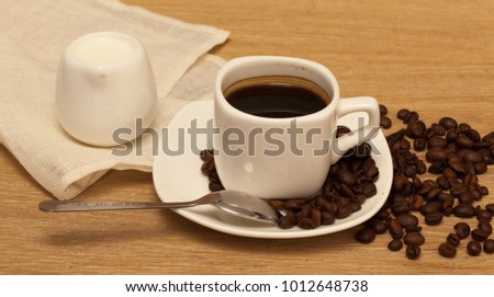 square coffee cup and cream stainless steel spoon oak background