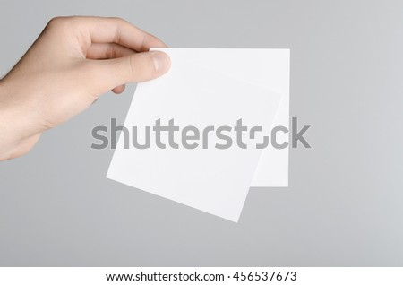 Square Flyer / Invitation Mock-Up - Male hands holding blank flyers on a gray background.