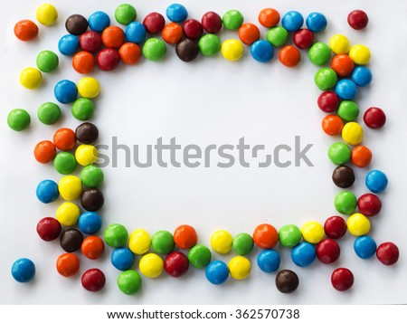 Square  frame look like sun of colorful chocolate candies on a white background with space for your text Valentines Day concept - stock photo