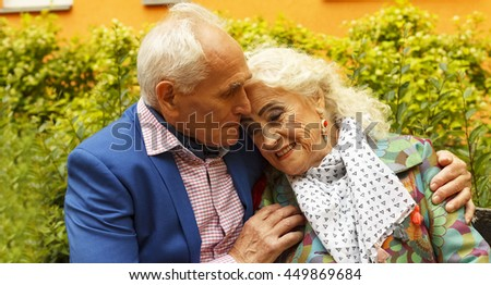 square image. Elderly man tenderly embracing his elderly wife on a bench near a residential building in a modern city. - stock photo