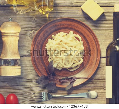 square image. Mock Up. Wine. Pasta. Cherry tomatoes. Top view. Closeup. Spices. Italian food ingredients on wooden background. - stock photo