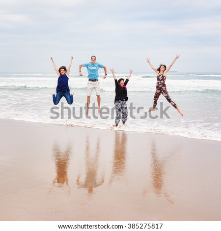 Square image of a family jumping on the beach