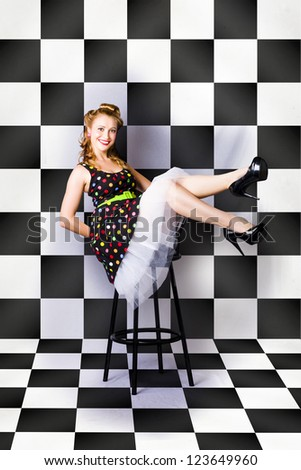 Square Image Of A Happy Retro Rockabilly Girl Sitting On A Bar Stool Inside A Vintage Diner In A Depiction Of Sixties American Culture - stock photo
