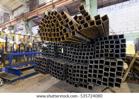 Square metal tube. Profiles stacked in a pile in the workshop of an industrial enterprise.