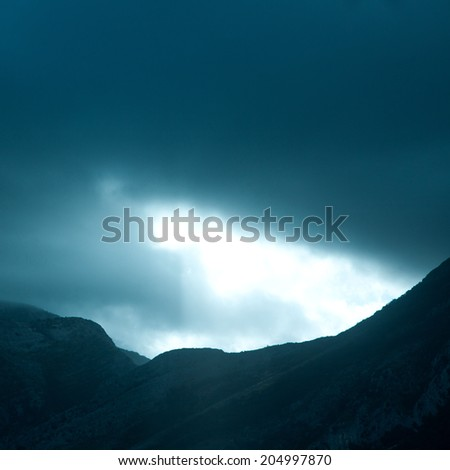 Square photo of dramatic rays of light pushing up through clouds - stock photo