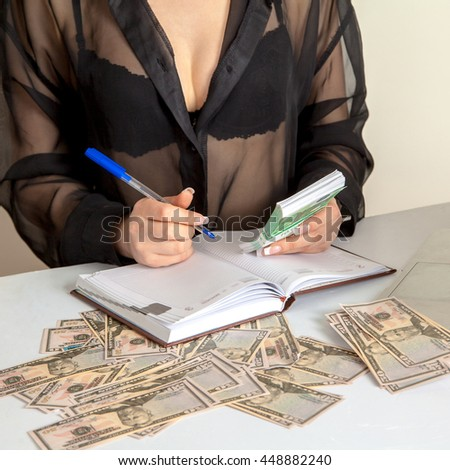 square photo of Girl accountant considers a large number of banknotes and making a notes