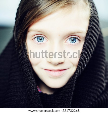 Square portrait of an adorable kid girl with big blue eyes wearing fashion knitted dark brown snood on the bricks wall background - stock photo