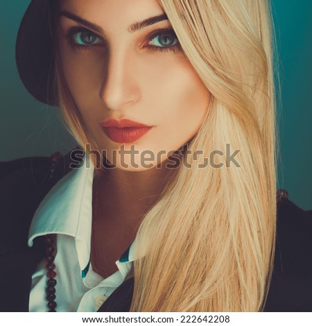 Square portrait of sexual blonde woman in studio on blue background - stock photo