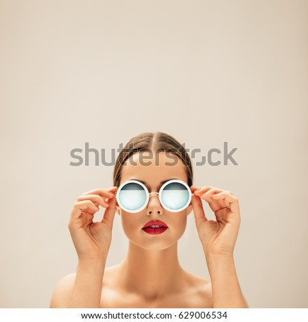 Square portrait of young woman with sunglasses against beige background. Caucasian female fashion model posing with glasses.