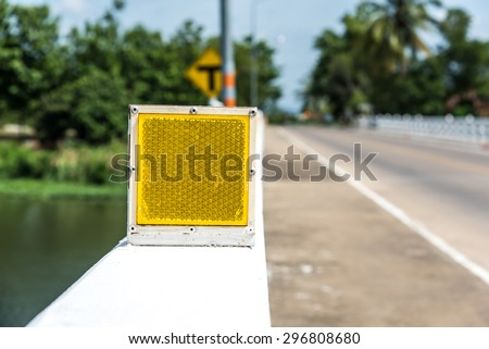 Square shape  yellow road reflector plate which mount on bridge barrier  - stock photo