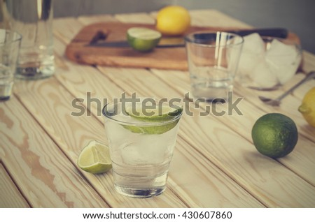 Square shot. Vodka, vodka in a glass with ice, lime, a cocktail bar, alcohol, alcoholic beverage. Closeup - stock photo