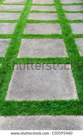 Square stones on grass - stock photo