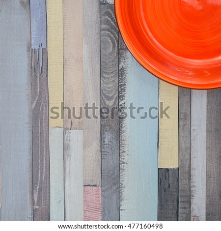 Square wooden background with a bright red plate in the corner