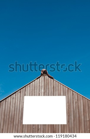 squared billboard on wooden structure (isolated on white) against a blue sky background - stock photo