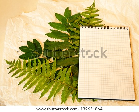 Squared notebook on the green leaves and crumpled paper background - stock photo