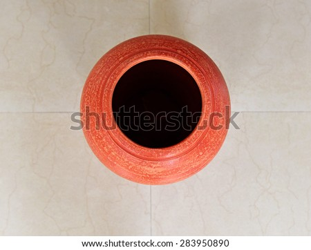Squares and circles. A red clay pot on tiled floor. view from top. Terracotta pot for interior decoration. Geometric lines and patterns. - stock photo