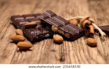 Squares of hazelnut chocolate on a heap with sweet almonds around and with pedig spiral in front are placed on wooden board with very worn surface. - stock photo