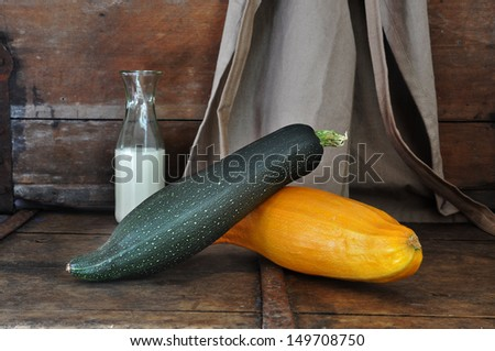 Squash on old wooden bench with milk bottle and apron vintage style. - stock photo