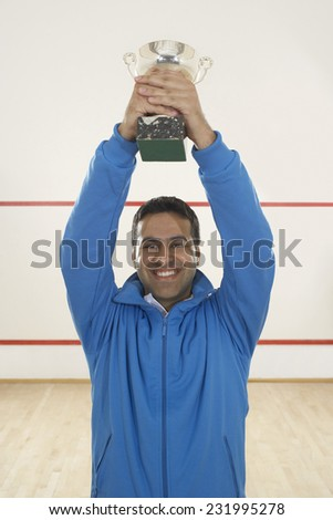 Squash Player Holding Trophy - stock photo