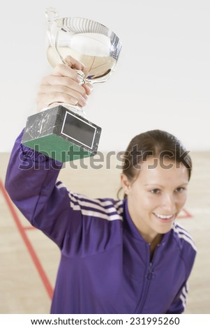 Squash Player Holding Up Trophy - stock photo