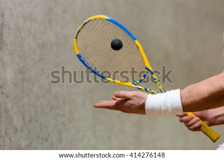 Squash racket and one ball closeup in man's hands. Sportsman or athlete playing squash game on court. - stock photo