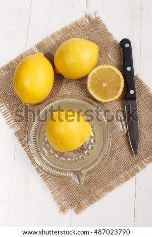 squeeze of lemon juice in a glass lemon squeezer with kitchen knife on jute
