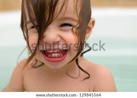 Squeezed eyed, teething toddler girl  giving a big laugh with wet hair.