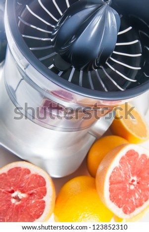Squeezer and fruits on white background - stock photo