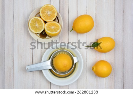 Squeezing lemons still life shot from a high angle on a rustic white wood kitchen table. - stock photo