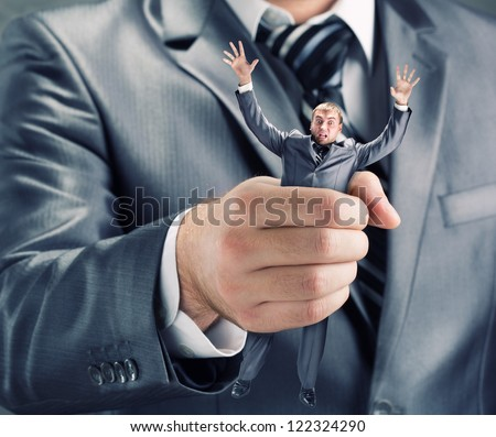 Squeezing small businessman in hand - stock photo