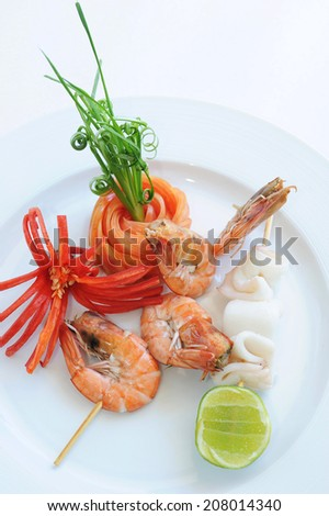 Squid and shrimp grilled on a plate decorated with tomato and red peppers. - stock photo