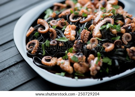 Squid ink tagliatelle with sliced octopuses and parsley - stock photo
