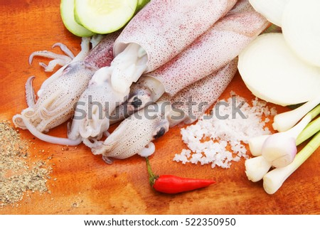 Squids with vegetables on cutting board