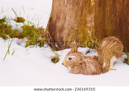 Squirrel toy in snow with tree trunk - stock photo