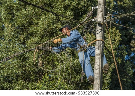 SRI LANKA, NUWARA ELIYA, 12.01.2012: worker repairing an electrical cable on a mast