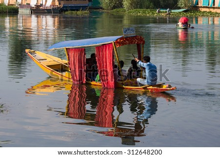 SRINAGAR, INDIA - JULY 03, 2015 : Lifestyle in Dal lake, local people use 'Shikara', a small boat for transportation in the lake of Srinagar, Jammu and Kashmir state, India