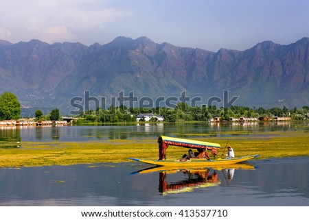 SRINAGAR, INDIA - JUNE 29, 2014 : Lifestyle in Dal lake, local people use 'Shikara', a small boat for transportation in the lake of Srinagar, Jammu and Kashmir state, India - stock photo