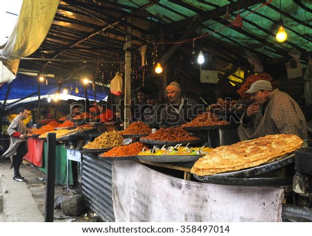 SRINAGAR KASHMIR CIRCA FEBRUARY 2012 - Unidentified food walah selling the colorful halwa paratha during the cold winter months in the market by the Hazratbal Mosque on the banks of Dal Lake. - stock photo