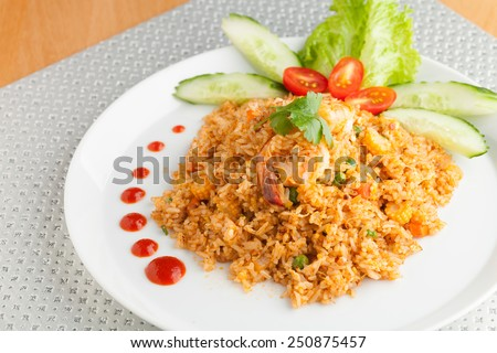 Sriracha shrimp fried rice dish with garnish dots of siracha sauce.