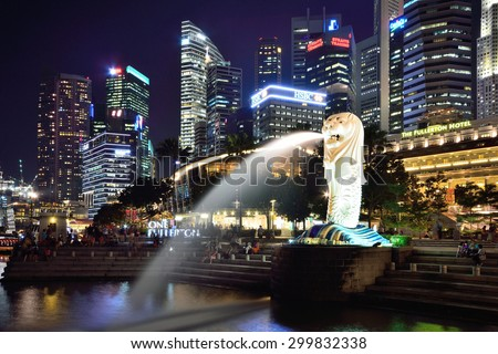 SSINGAPORE - APRIL 30,2015: Financial district skyscrapers and Merlion at Marina bay. The Merlion is a traditional creature with a lion head and a body of a fish, seen as a symbol of Singapore. - stock photo